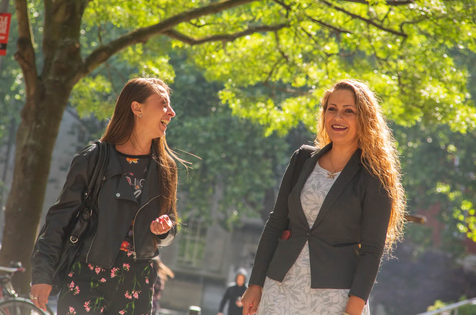 Two women smiling and walking