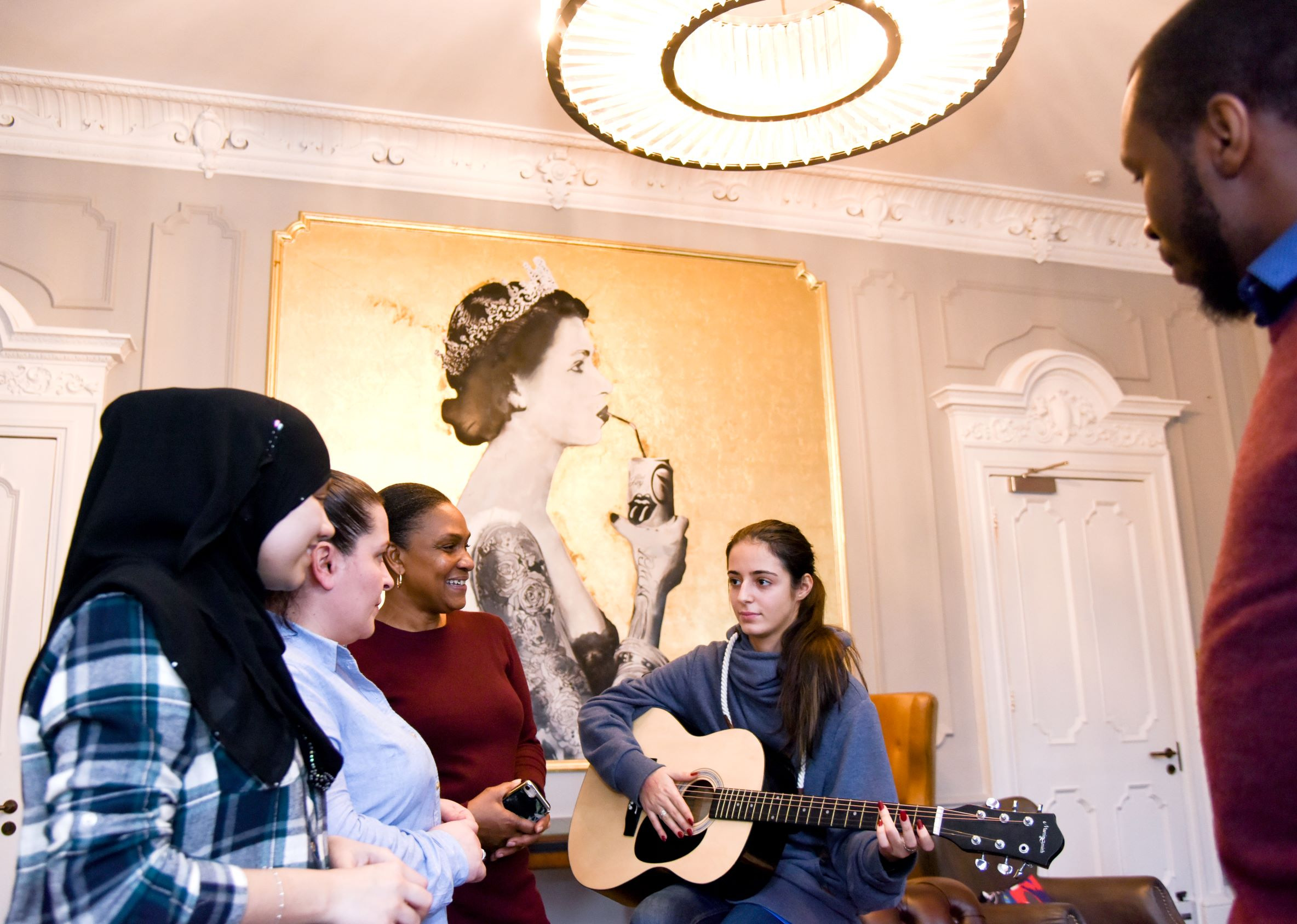 Woman playing guitar and students smiling